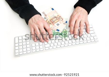 Man typing on computer keyboard, euro banknotes in front of him.