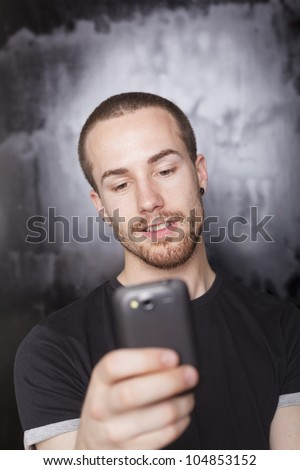 Man typing SMS with mobile phone, background is blured - stock photo