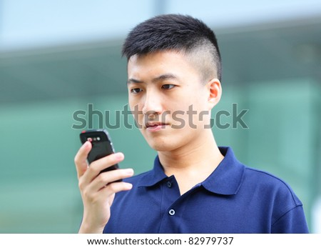 Man typing text message on mobile phone