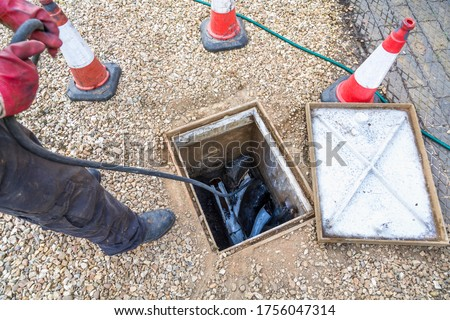 Photo of  Man unblocking domestic sewage drain through open inspection chamber, drain cleaning company, UK