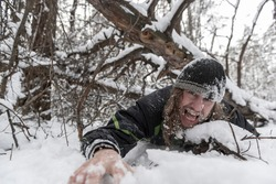 Man under a fallen tree struggles for his life in the winter forest. Danger of winter activities. Avalanche victim.