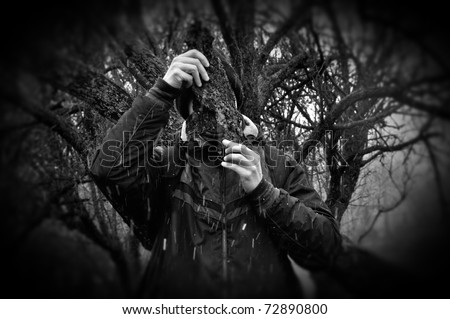 Man under branches obscured with bark peel snow storm in forest. Black and white.