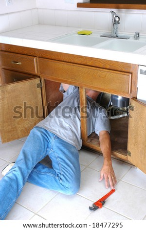 man under kitchen sink reaching for pipe wrench do it yourself home repair. Interior Design Ideas. Home Design Ideas