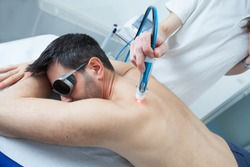 man undergoes laser treatment against skeletal muscle pain, laser can reduce inflammation in damaged tissues, relax muscles, and stimulate nerve regeneration