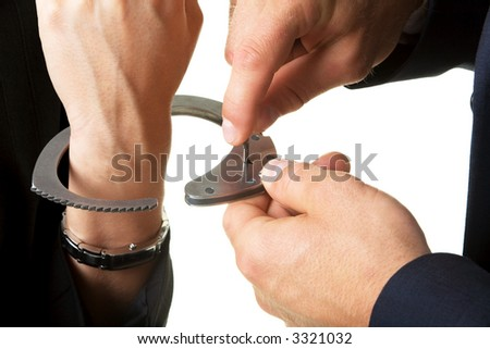man unlocking handcuffs that bind him to a woman (close-up) - stock photo