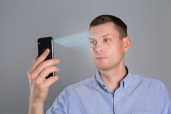 Man unlocking smartphone with facial scanner on grey background. Biometric verification