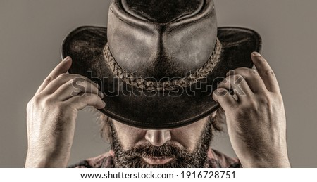 Man unshaven cowboys. American cowboy. Leather Cowboy Hat. Portrait of young man wearing cowboy hat. Cowboys in hat. Handsome bearded macho.