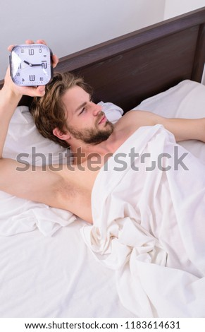 Man unshaven lay awake bed hold alarm clock. Stick sleep schedule same bedtime and wake up time. Man sleepy drowsy unshaven bearded face covered with blanket having rest. Sleep regime habits concept. #1183614631