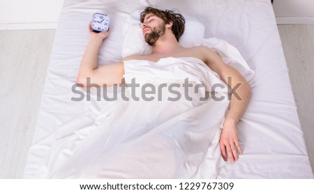 Man unshaven relaxing bed hold alarm clock. Man sleepy drowsy unshaven bearded face covered with blanket having rest. Guy lay under white bedclothes. Fresh bedclothes concept. Turn off alarm clock. #1229767309