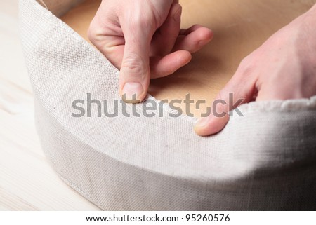 Man upholstering a round stool seat - stock photo