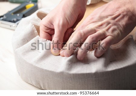 Man upholstering a round stool seat