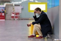 Man upset over flight cancellation, touches forehead, sitting in almost empty airport terminal due to coronavirus pandemic. Covid-19 outbreak worldwide Travel industry financial crisis. Force majeure.