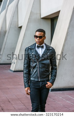 Man Urban Autumn/Spring Casual Fashion. Wearing black leather jacket, black jeans, sunglasses, white undershirt, black bow tie, a young African American guy walking on street in New York. City Boy.