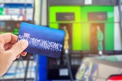 Man use credit card with blur image of gas station as background.(concept don't use mobile in gas station)