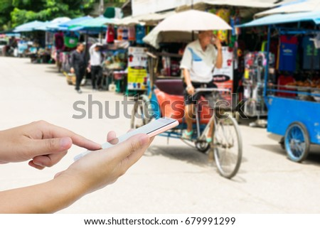Man use mobile ,blur image of tricycle taxi in street market as background. - Shutterstock ID 679991299