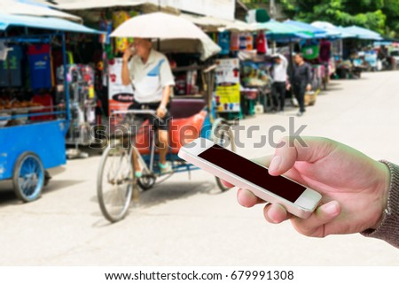 Man use mobile ,blur image of tricycle taxi in street market as background. - Shutterstock ID 679991308