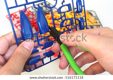 Man use nipper cutting a part of plastic model kit isolated on white background #516171118