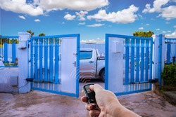 Man used hand remote control to open swing gate door by motor automation is home security system with blue cloud sky background.