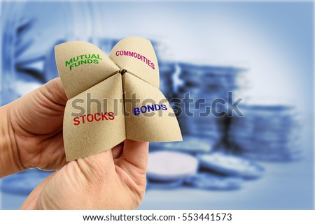 Man uses a paper fortune teller to make multiple decisions for his own portfolio, allocating assets and diversifying in a portfolio to minimize risk for optimal profits. Financial investment concept. Stock photo ©