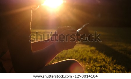Man uses a smartphone in the park at sunset in the summer, technology leisure concept