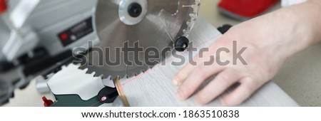 Man uses circular saw table while cutting laminate. Laminate laying technology with Click lock. Features of sawing laminate. Flooring option. Imitation shades and textures various types wood ストックフォト ©
