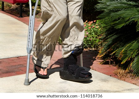 Man uses crutches along with a foot and ankle brace to help him walk after an accidental injury.