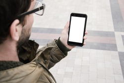 Man uses his Mobile Phone outdoor in the square, close up