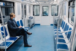 Man uses medical face mask, sits alone in metro carriage, commutes to work by public transport, avoids covid-19, uses equipment for staying safe during coronavirus pandemic. Health care concept