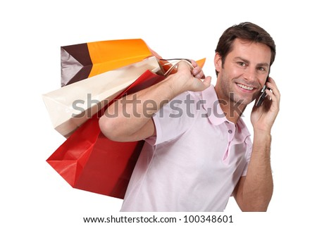 Man using a cellphone with bags of shopping