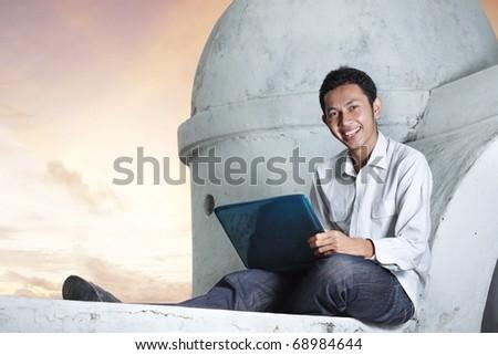 Man using a laptop outdoors