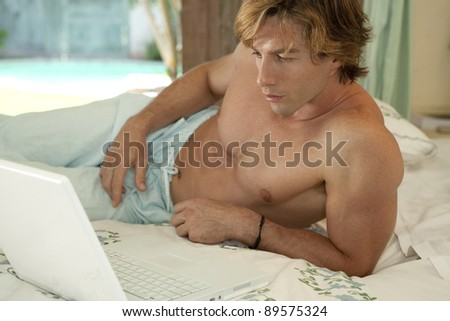 Man using a laptop while laying on bed.