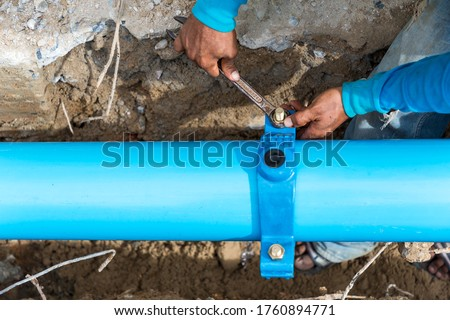 Man using a large wrench on water pipes. Construction site with new Water Pipes in the ground. Sewer pipes to repair or restore in street city.