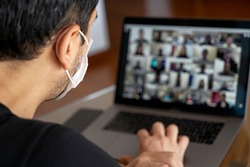 Man using a mask and having a video conference with work team amid COVID-19 pandemic.