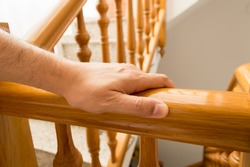 man using a railing to go downstairs at home