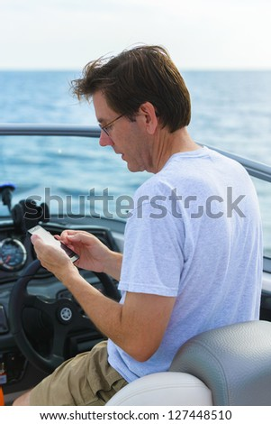 Man using a smart phone while boating.