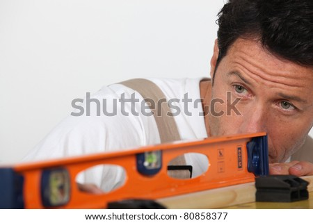 Man using a spirit level to check a surface
