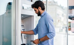 Man using a street ATM machine and withdrawing money