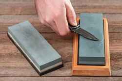 Man using a whetstone to sharp his pocket knife. Versatile foldable tool with razor-sharp blade.