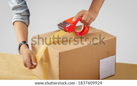 Photo of  Man using adhesive scotch tape, packing carton parcel box. Service worker holding tape preparing for transport. Sealing cardboard boxes with duct tape. Hand holding packing machine. White background.