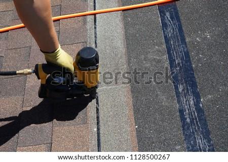 Man using air nail gun to attach asphalt shingles to roof.