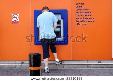 Man using ATM, cash machine, or hole in the wall. Sign on the wall/ the exterior about the services of a bank, also no smoking sign.
