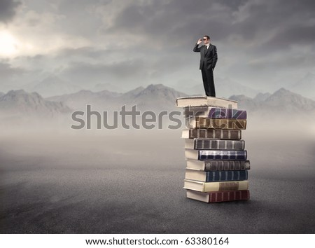 Man using binoculars standing on a stack of books in a desert