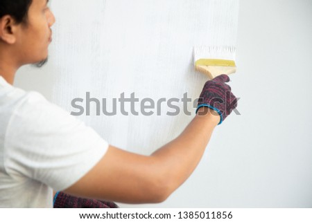 man using brush to repainting inside wall of the house #1385011856