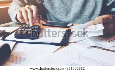 Man using calculator and calculate bills in home office.