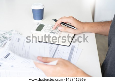 Man using calculator and calculate bills receipt in home expenses payments costs with paper note, financial account management and payment or saving concept