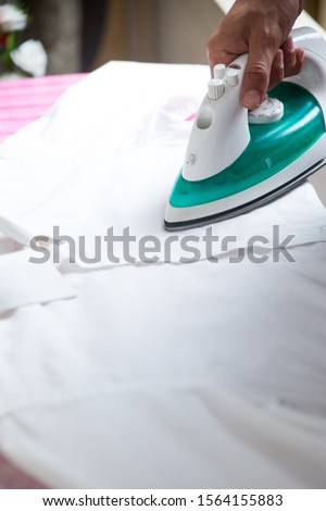 man using cordless iron to iron a white shirt over a pink ironing board #1564155883