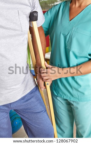 Man using crutches at physiotherapy with help of a physiotherapist