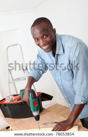 Man using electric drill at home