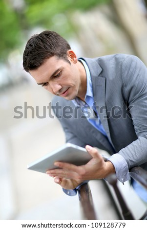 Man using electronic tablet outside in town