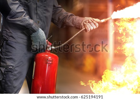 Man using fire extinguisher fighting fire closeup photo.